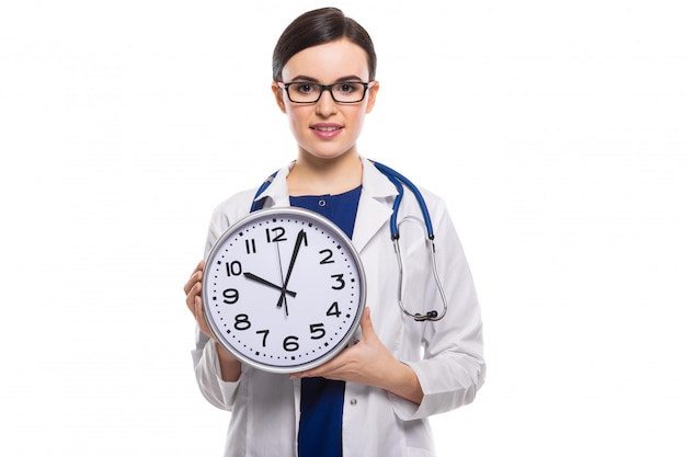 Young woman doctor with stethoscope holding clock in her hands in white uniform on white
