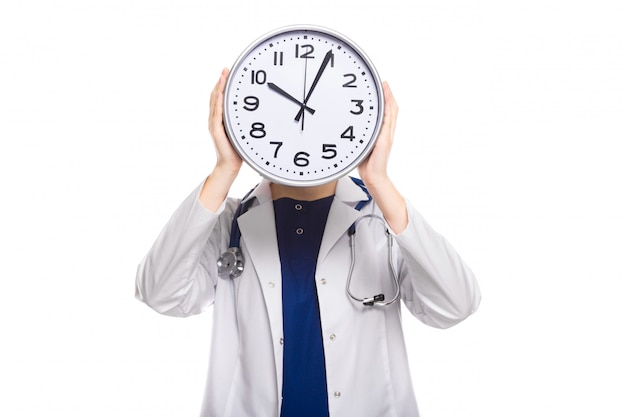 Young woman doctor with stethoscope in trouble holding clock in front of her head in white uniform