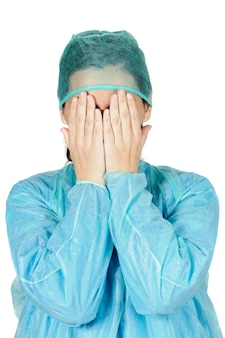 Young woman doctor worried with the hands in its face