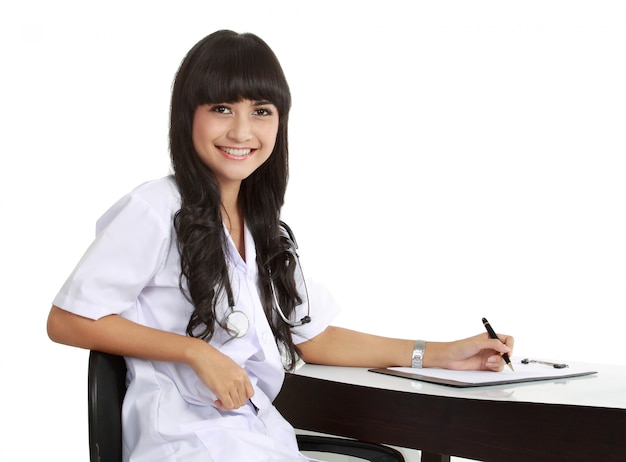 Young woman doctor writing prescription