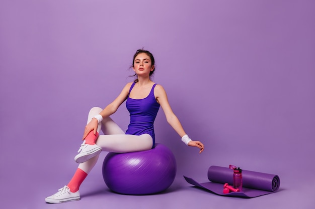 Young woman does aerobics on purple wall