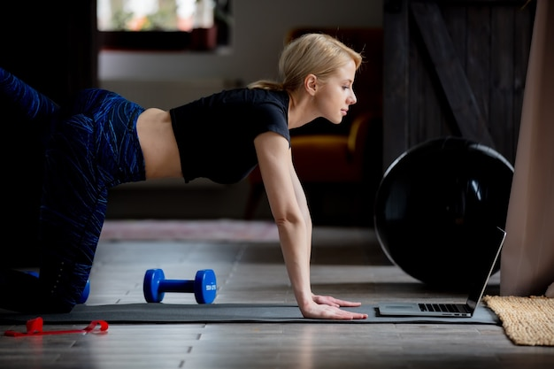 Young woman does sports exercises at home via the internet