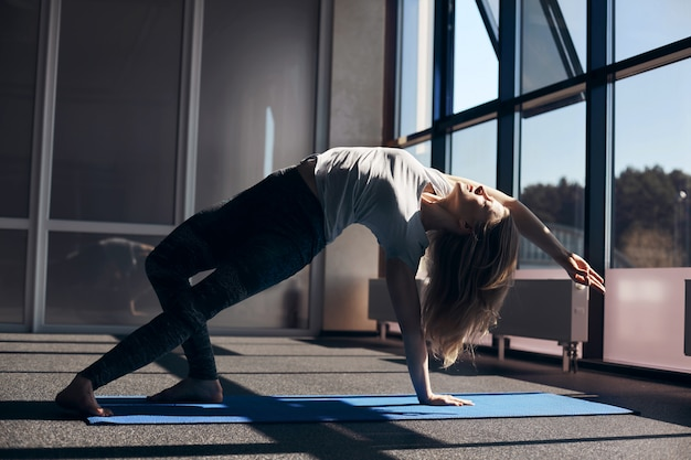 A young woman does yoga. the girl does an asana with a bend back, leans on her legs and one hand, the second hand is raised up. side view