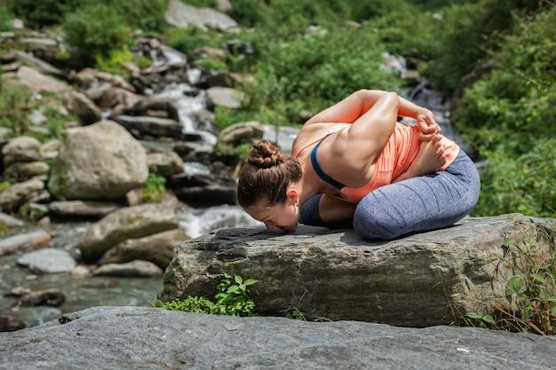 Молодая женщина занимается йогой на водопаде