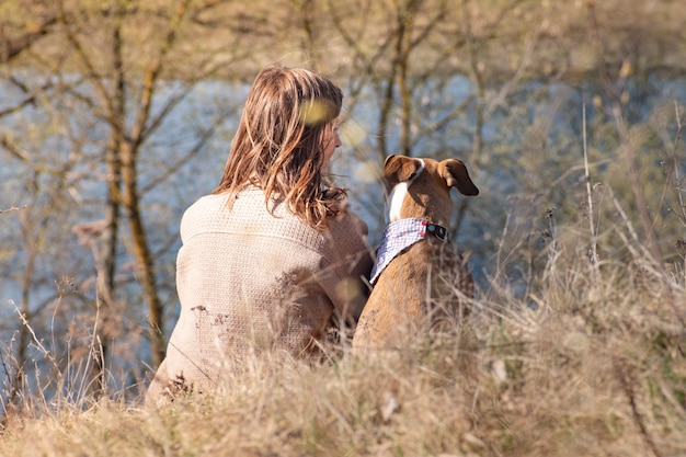Young woman and dog in bandana sit in grass near river on the hill