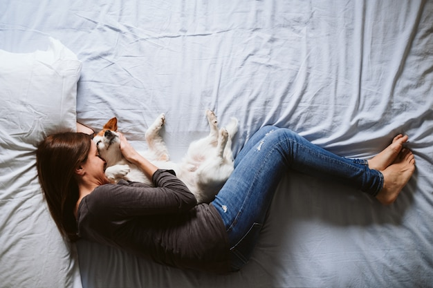 Young woman and dog at home resting on bed.