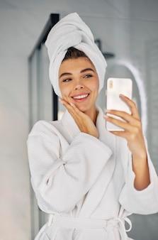 Молодая женщина делает красоту жить со своим телефоном Premium Фотографии