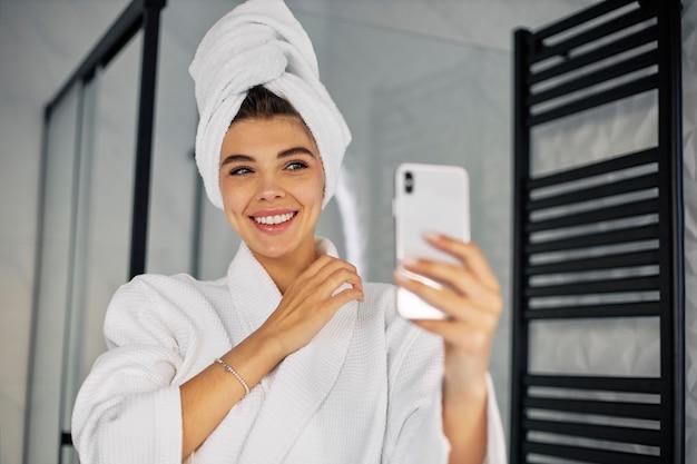 Молодая женщина делает красоту жить со своим телефоном