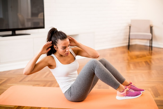 Young woman doing abs exercise in the room