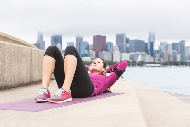 Young woman doing abs exercises with chicago skyline