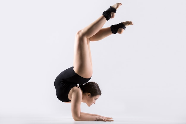 Young woman doing acrobatic handstand exercise