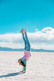 소금 호수에서 곡예를 하는 젊은 여자 프리미엄 사진