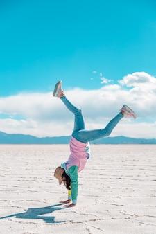 소금 호수에서 곡예를 하는 젊은 여자