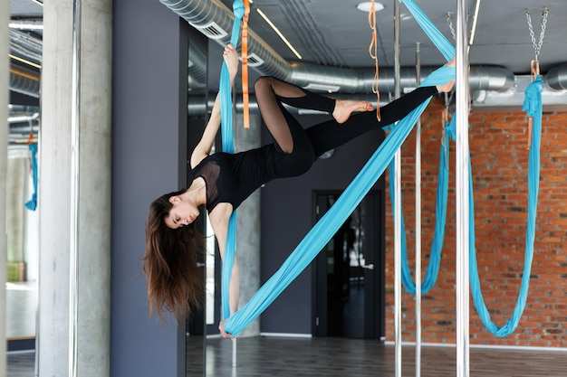 Young woman doing aerial yoga on blue hanging hammock in the gym