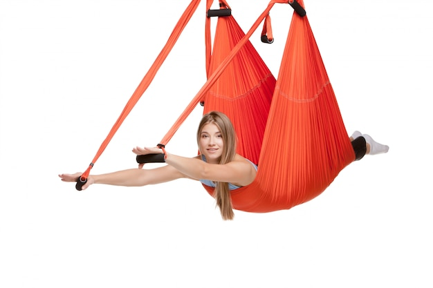 Young woman doing anti-gravity aerial yoga in hammock on a white wall