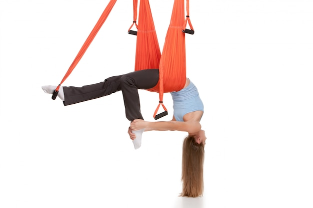 Young woman doing anti-gravity aerial yoga in hammock on white wall