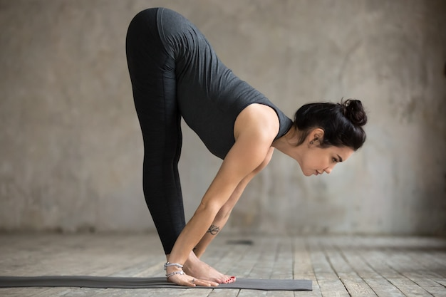 Young woman doing ardha uttanasana exercise