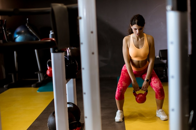 Young woman doing arm exercise with kettler dumbbell all in front of her