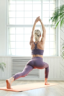 Young woman doing arm and leg stretching in the yoga center