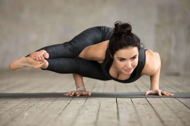 Young woman doing astavakrasana exercise
