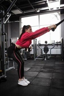 クロスオーバージムマシンで背中の筋肉のトレーニングをしている若い女性