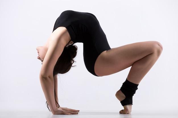 Young woman doing backbending exercise