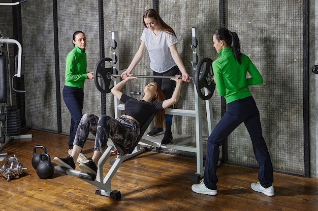 チームメイトのサポートを受けてジムでベンチプレスをしている若い女性