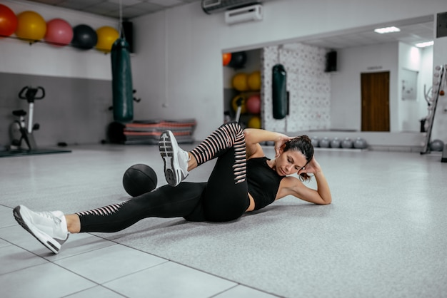 Young woman doing bicycle crunches at the gym.