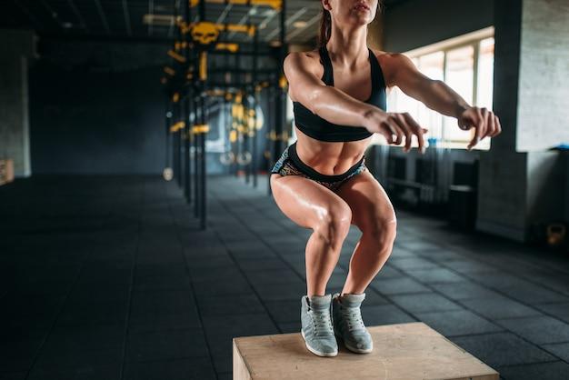 フィットネスクラブでボックスジャンプ運動をしている若い女性。ジムでの魅力的な女性アスリートトレーニング