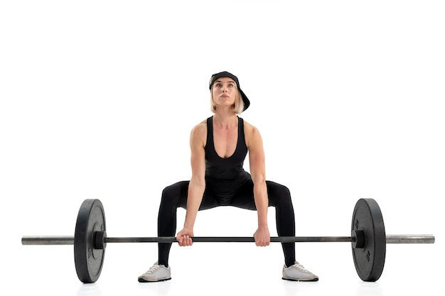 Young woman doing deadlift with a barbell isolated on white wall
