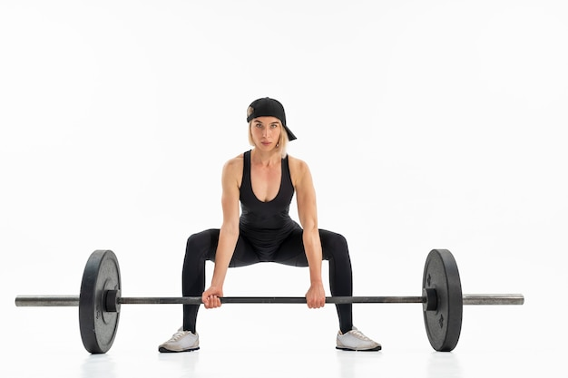 Young woman doing deadlift with a barbell isolated