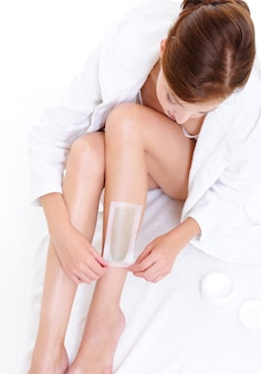 Young woman doing depilation for her legs with waxing
