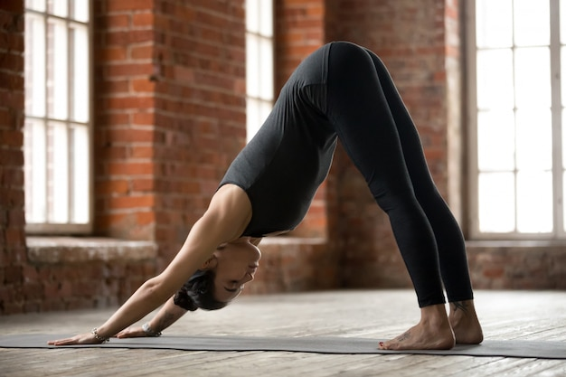 Young woman doing downward facing dog exercise