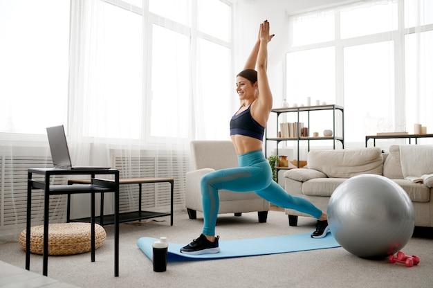 Молодая женщина делает упражнения дома, онлайн обучение пилатесу на ноутбуке. женский человек в спортивной одежде, спортивная тренировка в интернете, интерьер комнаты