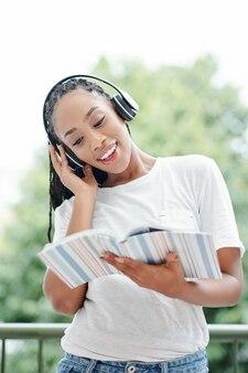 Молодая женщина делает упражнения в учебнике английского языка, она слушает спикер в наушниках и повторяет за ним