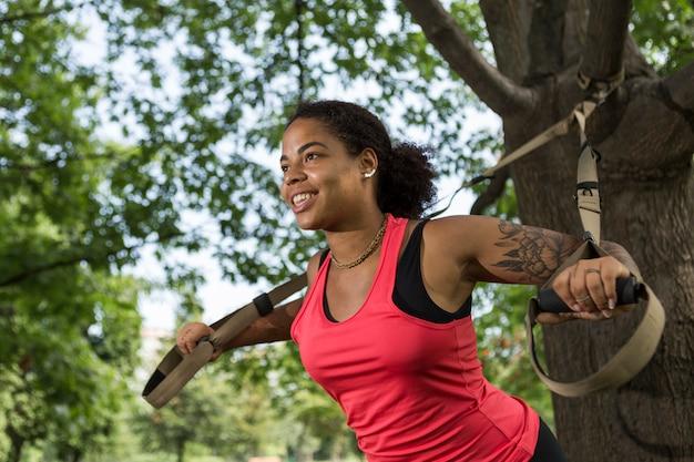 Молодая женщина делает упражнения в парке