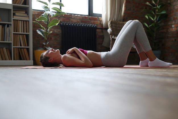 Молодая женщина делает упражнения дома