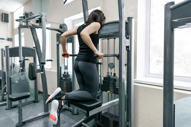 Young woman doing exercises for the back on fitness machine