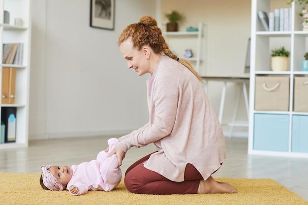 Молодая женщина делает упражнения для своей девочки, лежа на полу в комнате