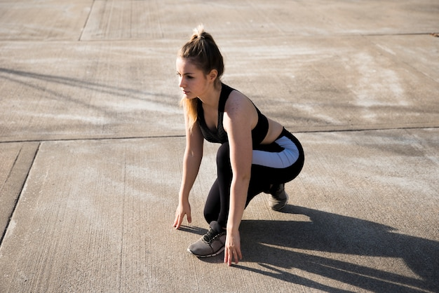 Young woman doing exercises at the street