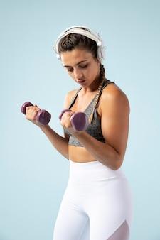 Молодая женщина делает упражнения с наушниками на