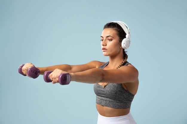 ヘッドフォンをつけたまま運動をしている若い女性