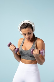 Young woman doing exercises with her headphones on