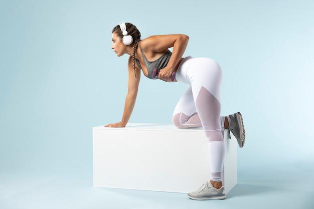 Giovane donna che fa esercizi con le cuffie addosso