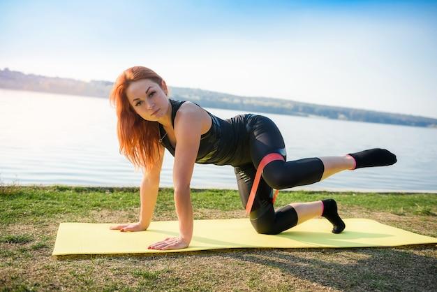 昼間に湖の近くの屋外でレジスタンスバンドで運動をしている若い女性。健康的な生活様式