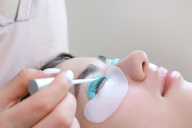 Молодая женщина делает процедуру ламинирования ресниц в салоне красоты, крупным планом