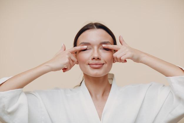 얼굴 체조 자기 마사지와 활력 운동을하는 젊은 여자