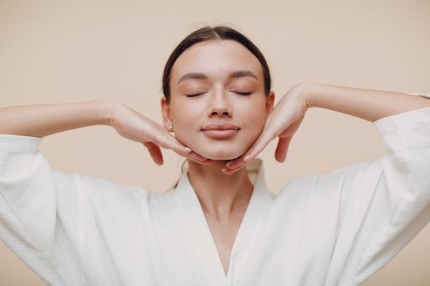 Молодая женщина делает массаж лица йоги лицевой гимнастики самомассаж и омолаживающие упражнения