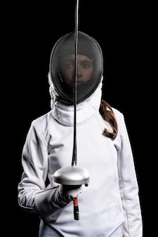 Young woman doing fencing in special equipment