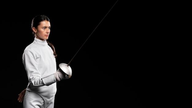 Молодая женщина занимается фехтованием
